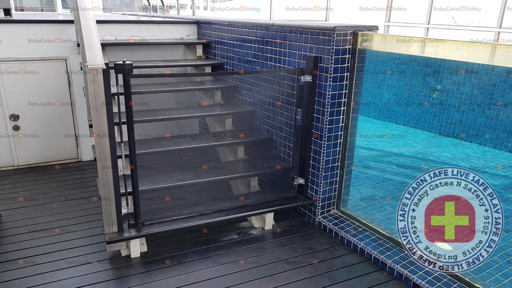 Black Retract-A-Gate Retractable Gate engaged at the entrance of penthouse swimming pool