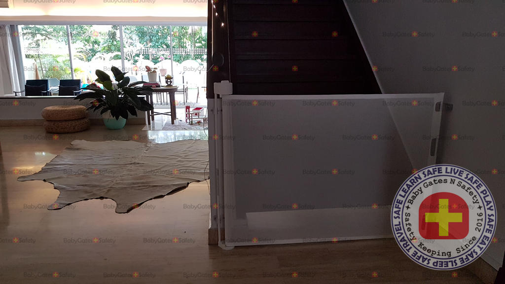 White Retract-A-Gate retractable gate used at bottom of stairs